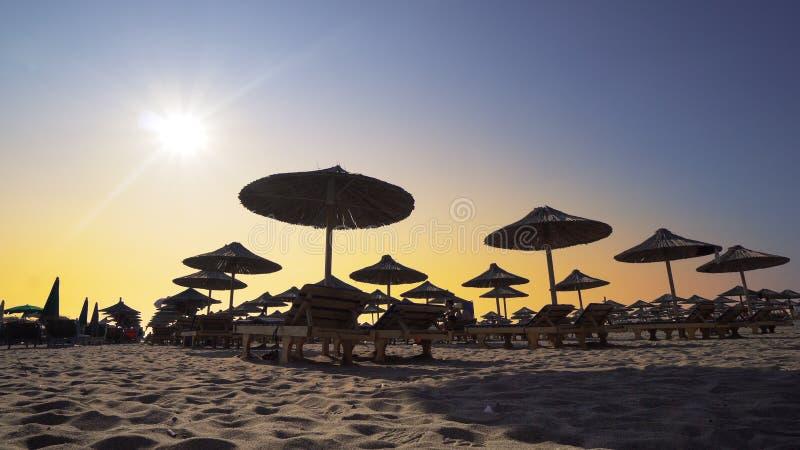 Strandstolar med paraplyet på stranden på solnedgången arkivbild