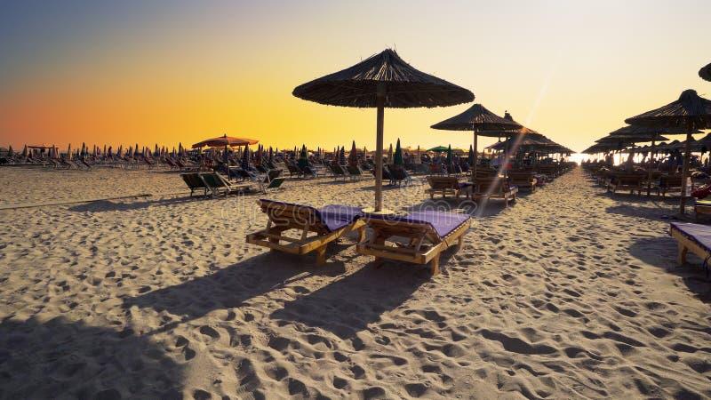 Strandstolar med paraplyet på stranden på solnedgången arkivfoto