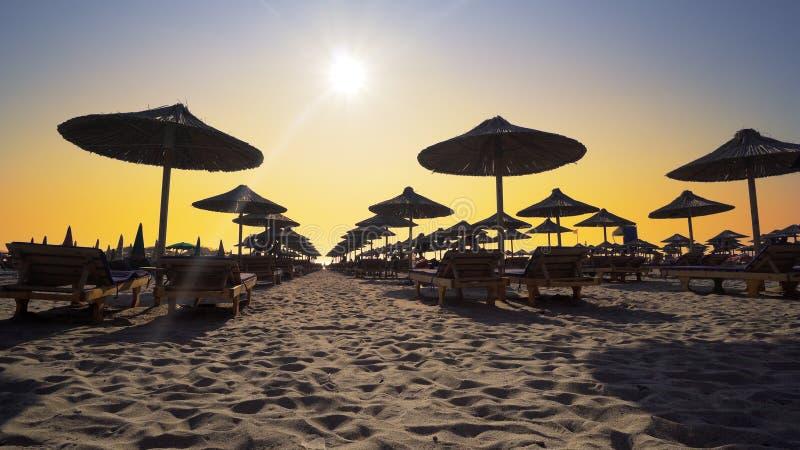 Strandstolar med paraplyet på stranden på solnedgången royaltyfri fotografi