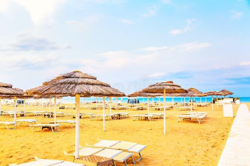 Strandstolar och paraplyer i Rimini, Italien under sommardag med blå himmel Sommarsemestern och kopplar av begrepp royaltyfri bild