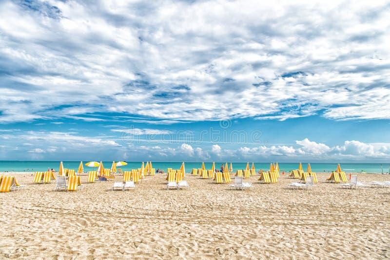 Strandstolar och paraplyer på molnig himmel i miami, USA Havsstrand med vit sand och blått vatten på solig dag Sommarsemester på royaltyfria bilder