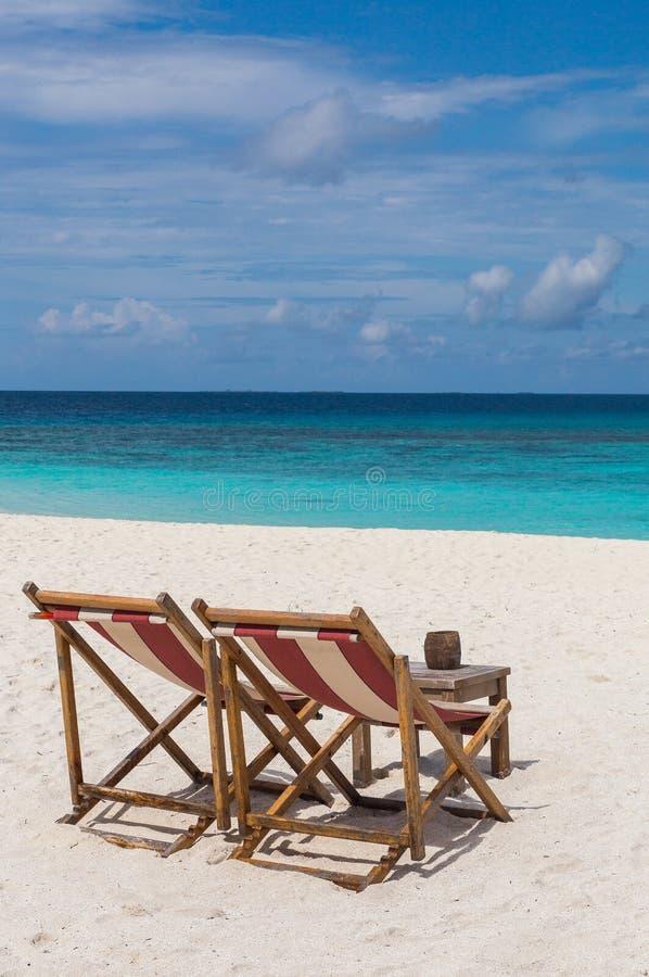 Strandstolar på strandatollön Maldiverna royaltyfri bild