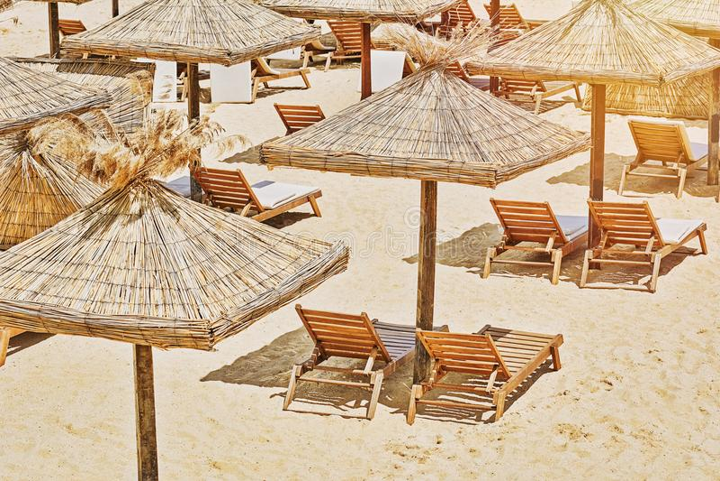 strandstolar varar slö paraplyer royaltyfria foton
