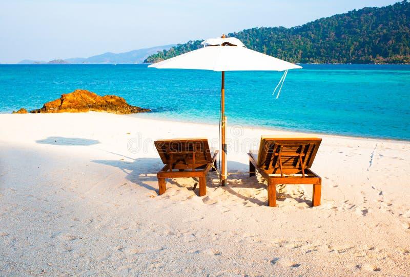 Strandstolar vid havet - tropiska semesterbakgrund royaltyfria bilder