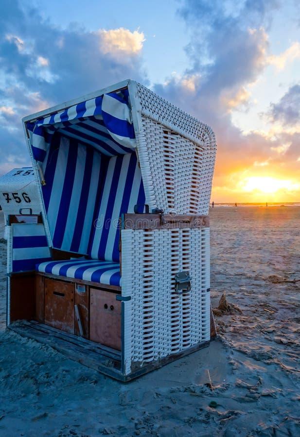 Strandstuhl auf dem sandigen Strand bei Sonnenuntergang auf der Nordsee lizenzfreies stockfoto