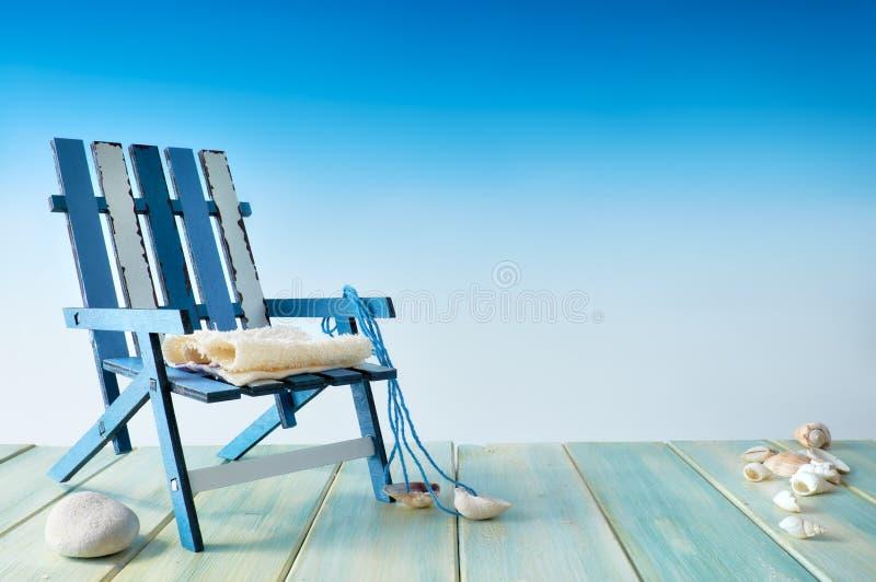 Strandstuhl auf hölzerner Terrasse mit Seeoberteilen, Küste decoratio stockfoto