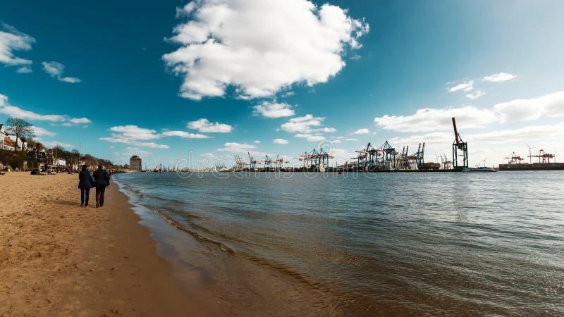 Strandszene bei der Elbe mit Behälterhafen in Hamburg stockbilder