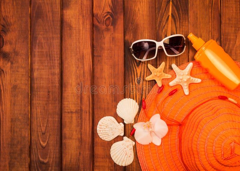 Strandtillbehör: hatt, sunscreen och solglasögon, sjöstjärna, hav arkivbilder