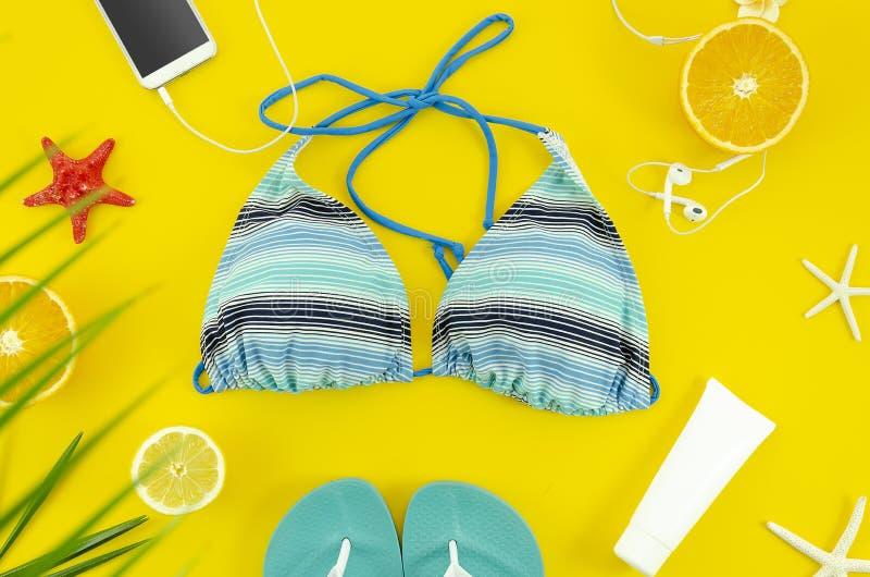 Strandtillbehör med bikinin, smartphonen, kruset och häftklammermatare För sommartur för bästa sikt plant lekmanna- begrepp royaltyfri bild