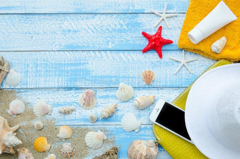 Strandtillbehör på den blåa träplankabakgrunden - sand, snäckskal, röd stjärna, handduk, mobiltelefon, solkräm och arkivbilder
