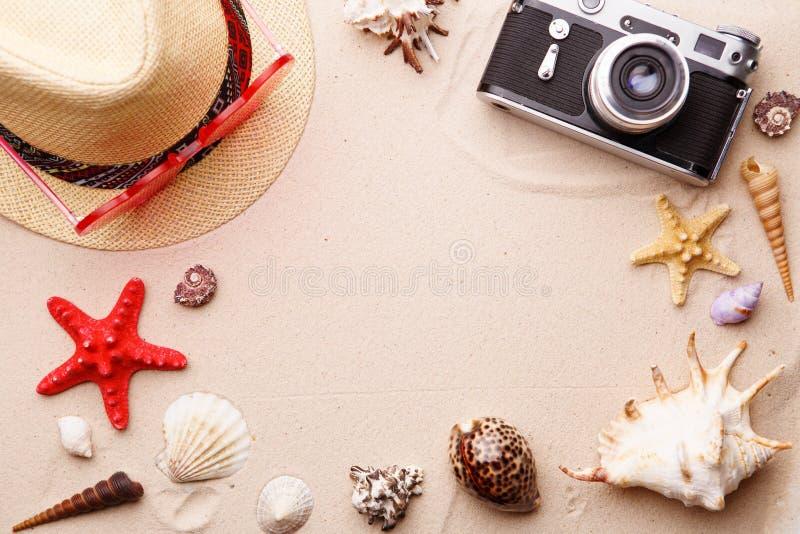 Strandtoebehoren - zonnebril, hoed en camera op zand witn shells en seastar stock foto's