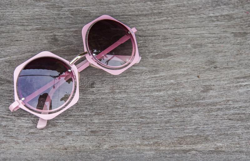 Strandurlaubkonzept - nahe hohe rosa nette Frauensonnenbrille auf Tabelle lizenzfreie stockfotografie