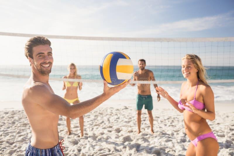 strandvänner som leker volleyboll royaltyfri foto