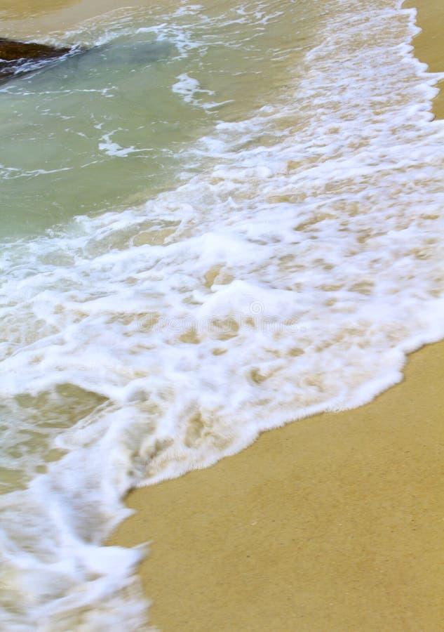 Strandvågor bryter till kusten arkivfoton
