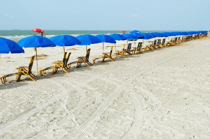 Strandvardagsrumstolar med paraplyer arkivbild