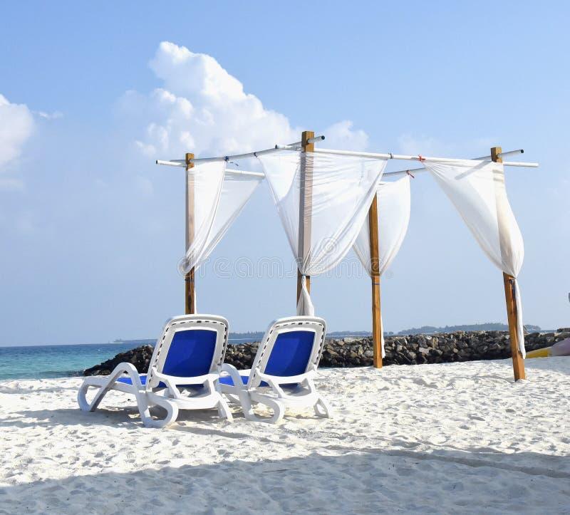 Strandvikningstol på stranden royaltyfri foto