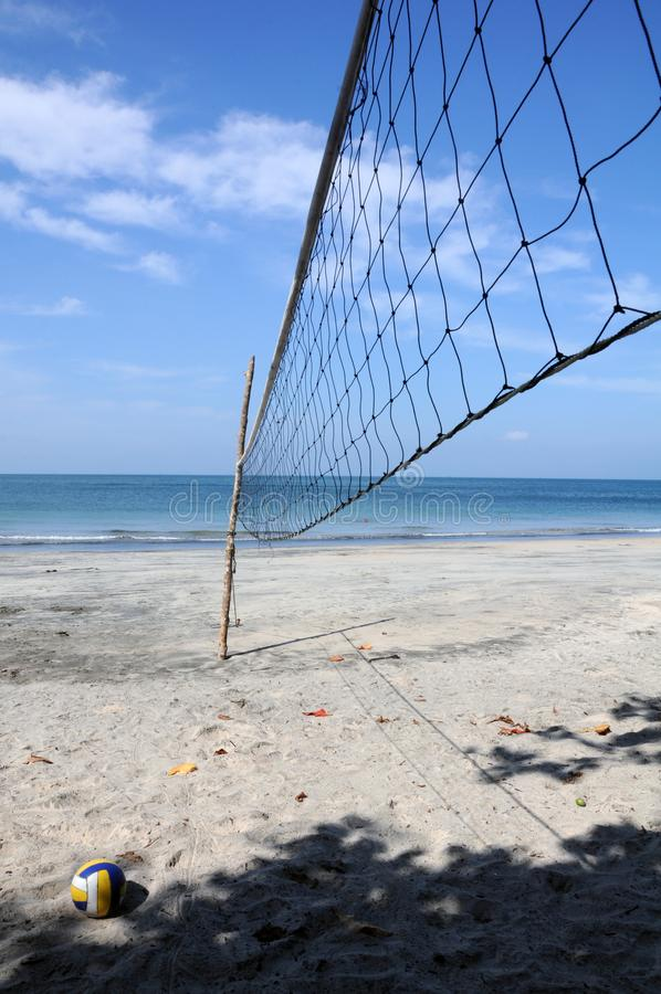 Strandvolleyboll på sanden under solljus och blå himmel royaltyfri bild