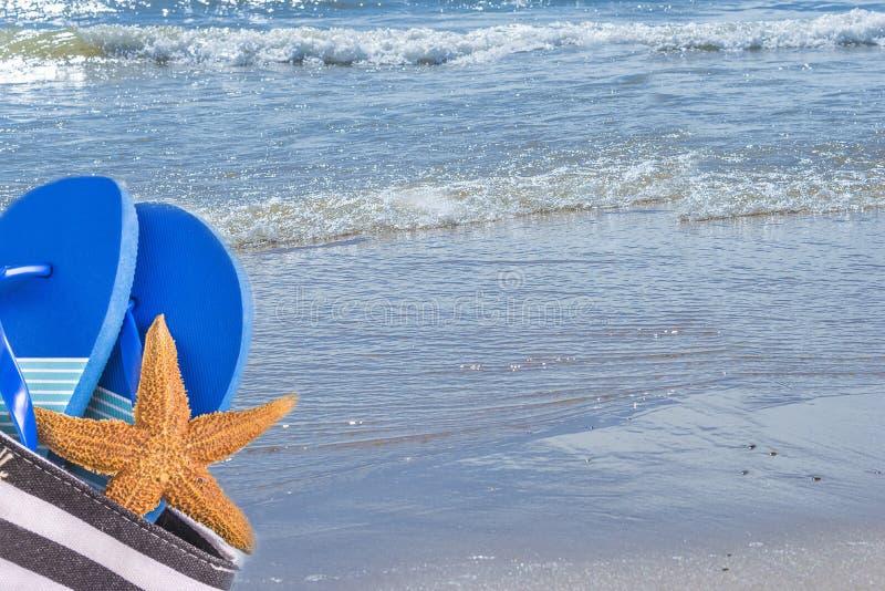 Strandzak met blauwe tong en zeester op de mooie oceaan royalty-vrije stock afbeelding