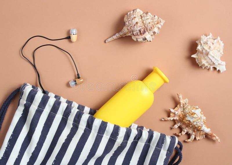 Strandzak, zeeschelpen, oortelefoons, fles bruine kleurroom op een bruine achtergrond, strandseizoen, rust op het overzees Hoogst stock fotografie