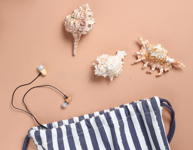 Strandzak, zeeschelpen, oortelefoons op een bruine achtergrond, strandseizoen, rust op het overzees De hoogste mening, vlakke min stock afbeeldingen