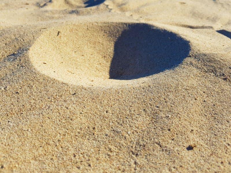 Strandzand dat een kleine kegel zoals een zandvulkaan heeft gevormd stock foto