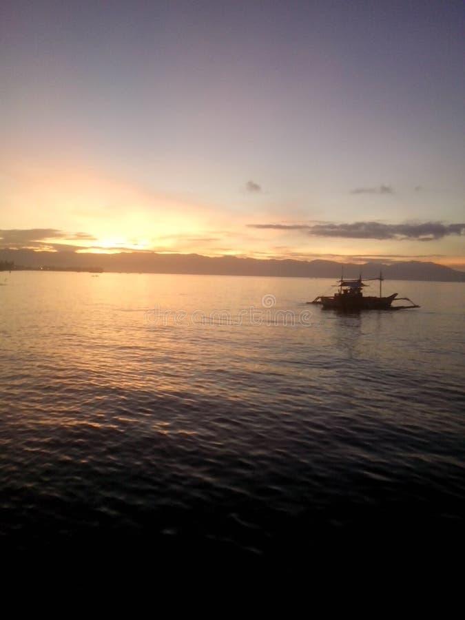 Strandzonsopgang met motorboot stock afbeeldingen
