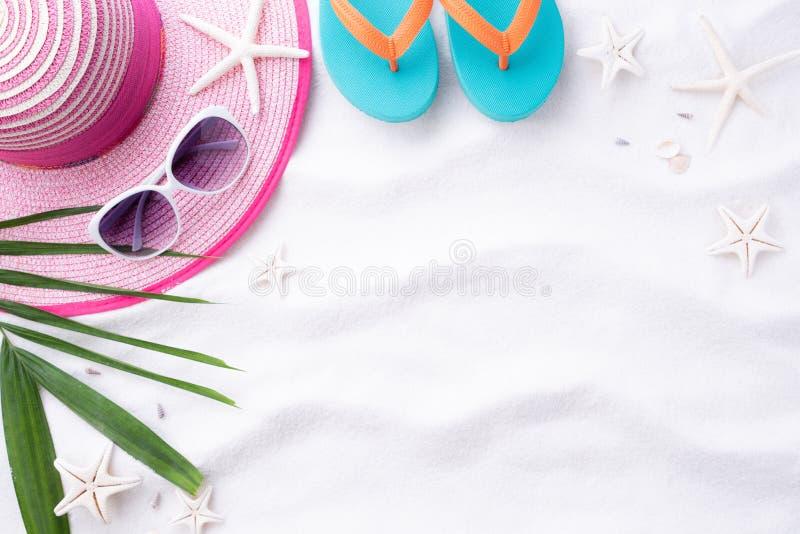 Strandzus?tze gr?nen tropische Bl?tter mit Sonnenbrille, Flipflop Starfish, Strandhut und Seeoberteil auf wei?em Sandstrand backg lizenzfreie stockbilder