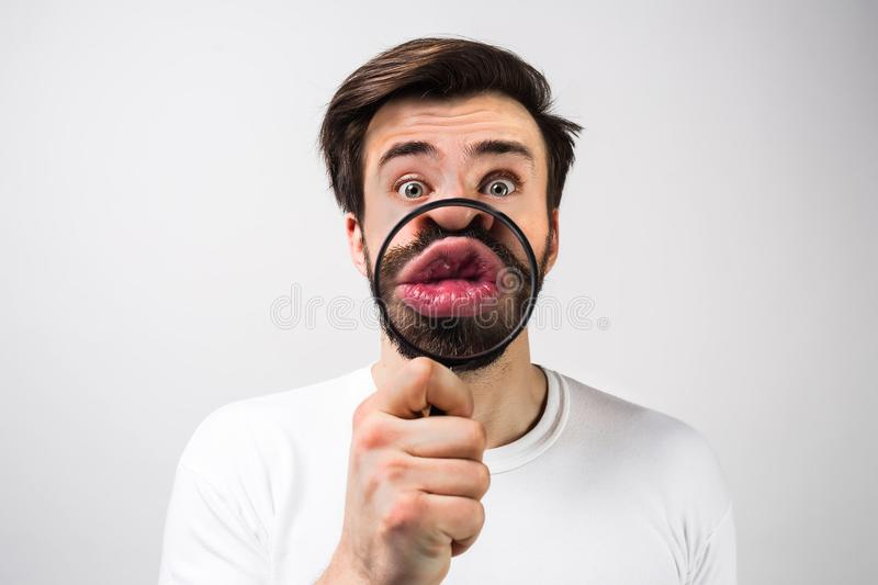 Strange and amazed man on white background and making some fun with putting a loupe in front of his mouth. Guy royalty free stock photos