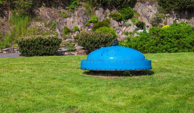 Strange blue ufo. On grass field royalty free stock photography