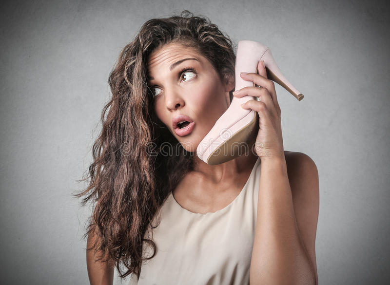 A strange call. A woman is doing a strange call using a high heeled shoe royalty free stock photo