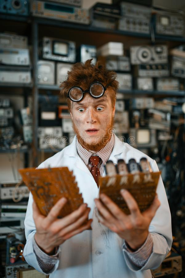 Strange engineer looks on electronic chips in lab. Oratory. Electrical testing tools on background. Lab equipment, engineering workshop stock photos