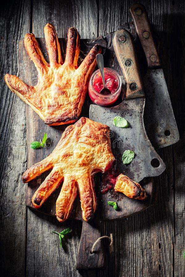 Strange hand cake with a chopper as concept of liking. On wooden table stock images