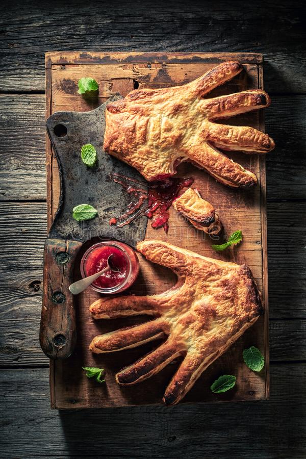 Strange hand cake with a chopper as liking concept. On wooden table royalty free stock image