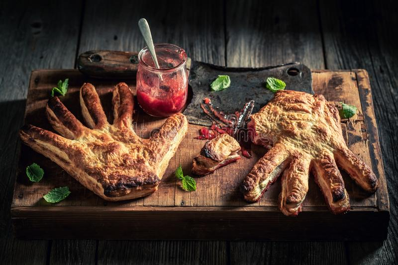 Strange hand cake with strawberry jam as liking concept. On wooden table stock photo