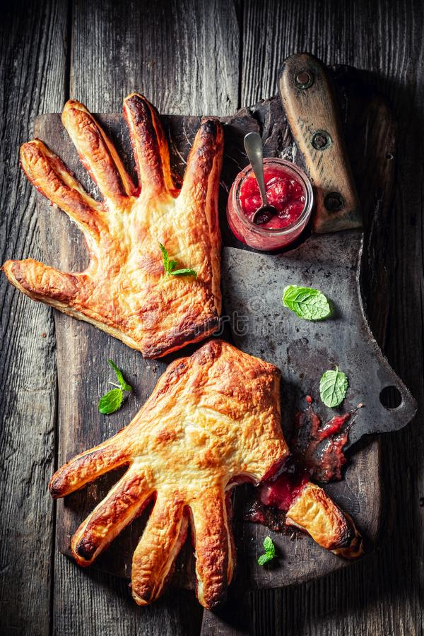 Strange hand cake with thumb cut off as liking concept. On wooden table royalty free stock images