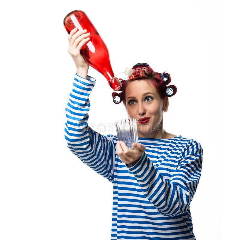 Strange housewife holding an empty bottle of wine and glass on a white background. Concept female alcohol addiction stock photography