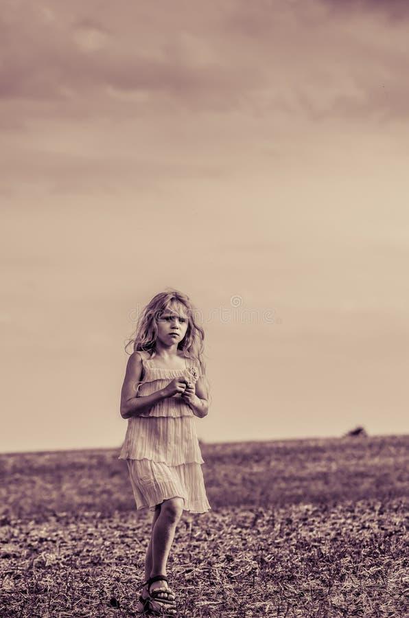 Strange image of girl alone in the field stock photo