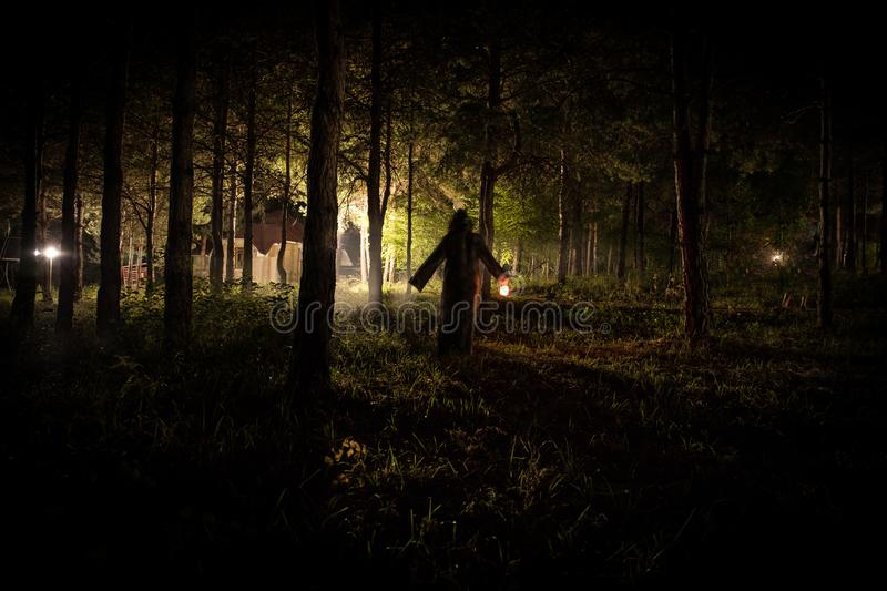 strange light in a dark forest at night. Silhouette of person standing in the dark forest with light. Dark night in forest at fog royalty free stock photography