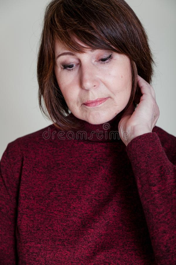 Strange mood. Close-up portrait old woman with thoughtful look. Strange look. Close-up portrait of a woman without retouching sitting on a bright monophonic stock image