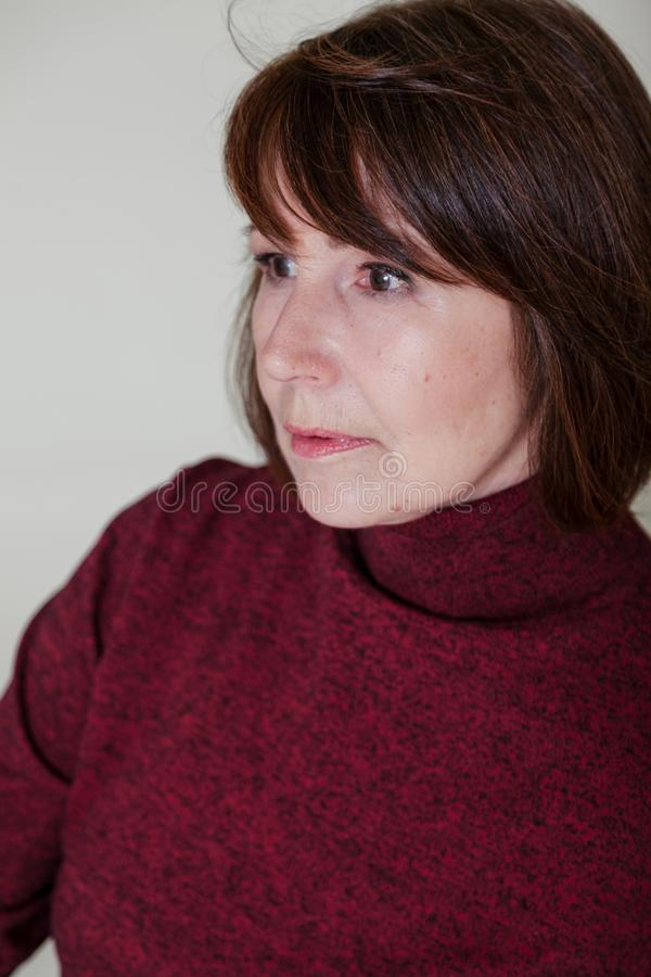 Strange mood. Close-up portrait old woman with thoughtful look. Strange look. Close-up portrait of a woman without retouching sitting on a bright monophonic stock photos