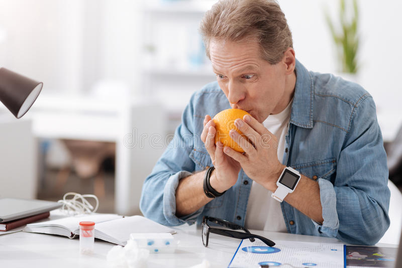 Strange male person kissing orange. Delicious fruit. Delighted man wearing jeans shirt wrinkling his forehead holding elbows on the table royalty free stock photo