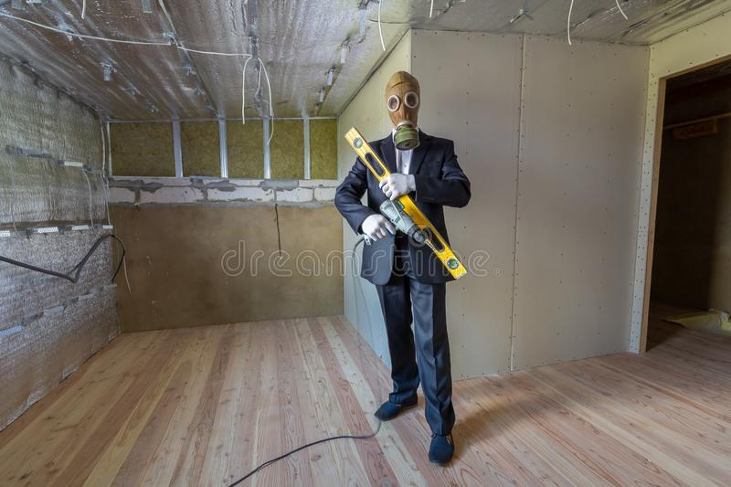 Strange man in businessman suit and gas protection mask inside a room under renovation works holding electric screwdriver and a royalty free stock photos