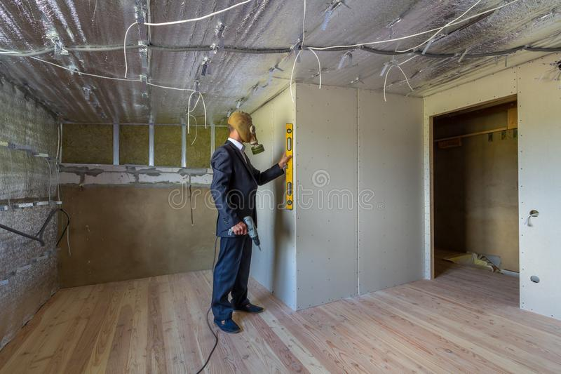 Strange man in businessman suit and gas protection mask inside a room under renovation works holding electric screwdriver and a stock photos