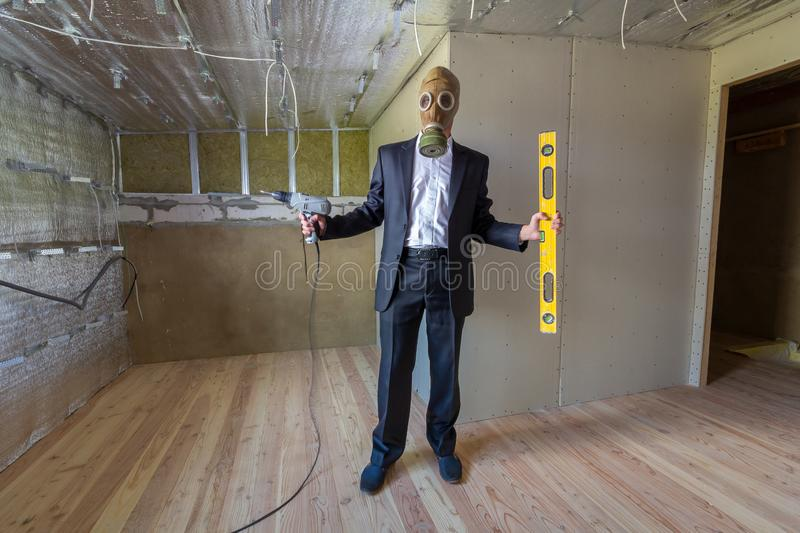 Strange man in businessman suit and gas protection mask inside a room under renovation works holding electric screwdriver and a royalty free stock image