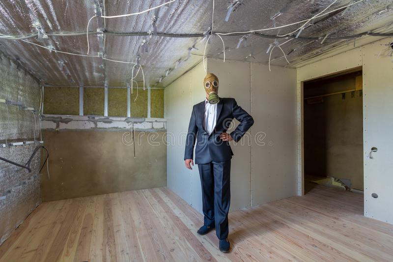 Strange man in businessman suit and gas protection mask inside a room under renovation works stock images