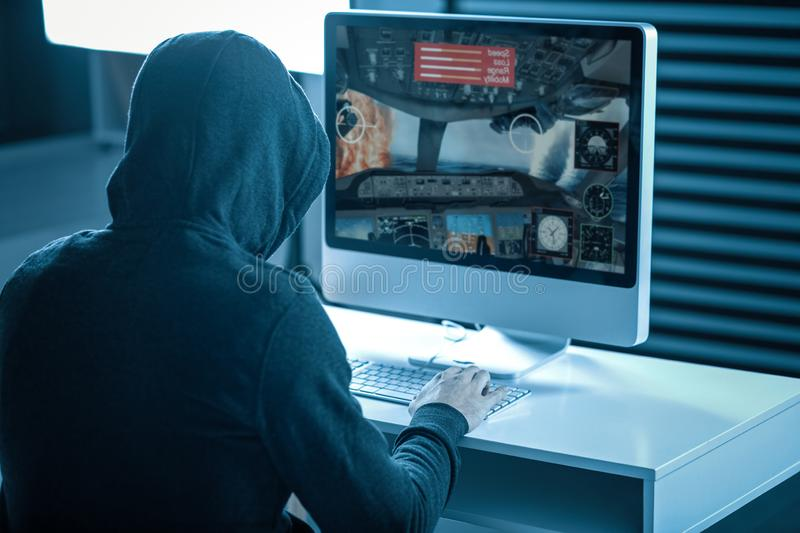 Strange man in a hood playing computer games. Favorite game. Strange man in a hood playing computer games sitting at home stock image