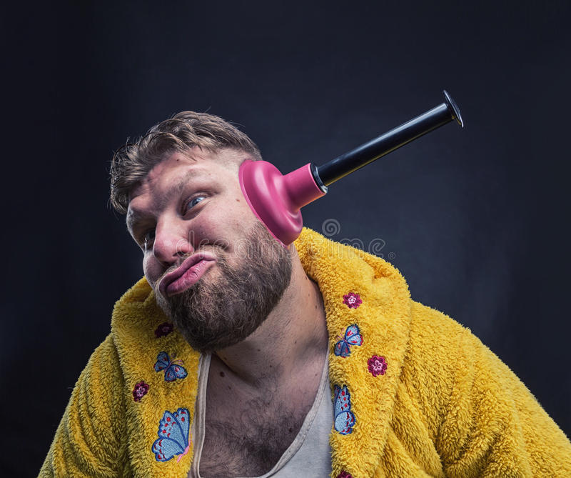 Strange man with a plunger in his ear. Strange man in a terry bathrobe with a plunger in his ear stock image