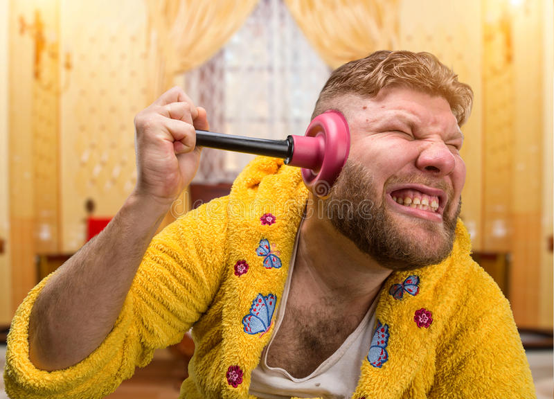 Strange man with a plunger in his ear. Strange man in a terry bathrobe is cleaning his ear by a plunger in his ear in home interior royalty free stock images