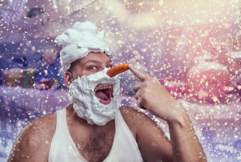 Strange man with shaving foam pointing at his nose. Smiling man with shaving foam points at his carrot nose over winter background stock image