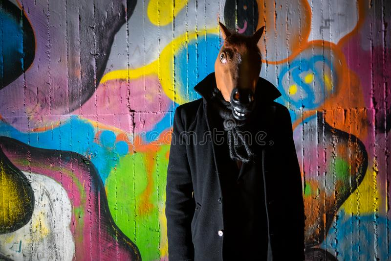 Strange man wearing a scary horse mask in night stock images